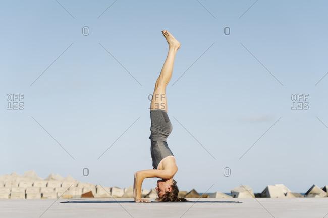 Female sportsperson doing headstand on exercise mat