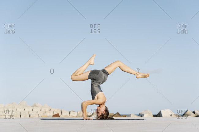 Sportswoman doing headstand with legs apart against clear sky