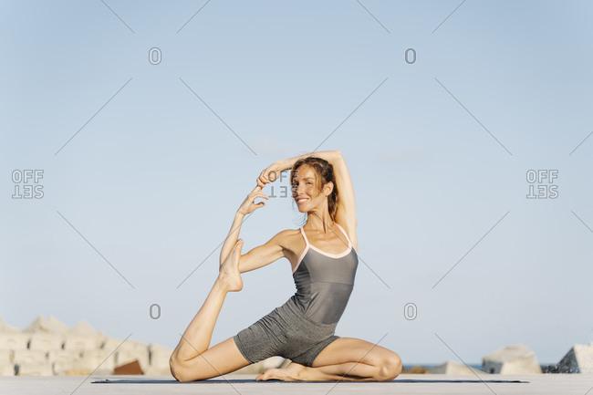 Smiling female sportsperson doing yoga on exercise mat