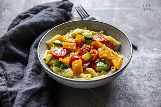 Bowl of vegan pasta with pumpkin- tomatoes and zucchini