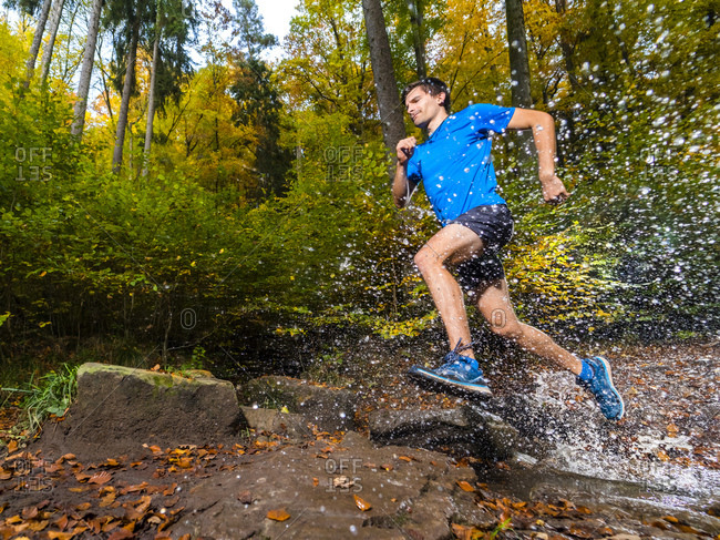 Young male sportsperson splashing water while trail running in autumn forest at Kappelberg- Germany