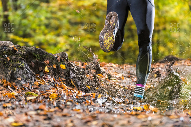 Male trail runner running through mud in autumn forest at Kappelberg- Germany