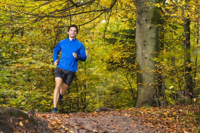 Smiling male athlete trail running over mud in autumn forest at Kappelberg- Germany