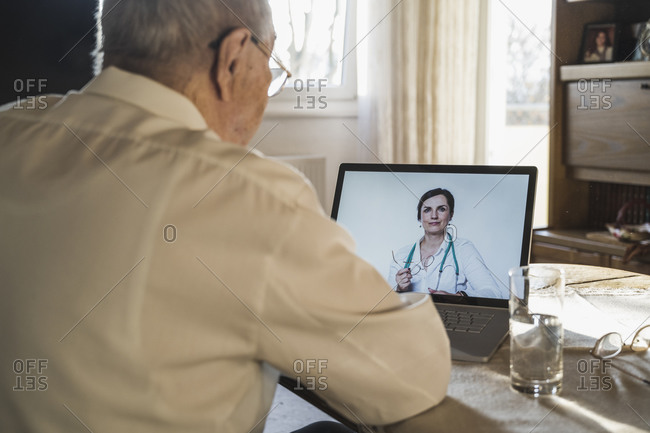 Female doctor consulting senior man on laptop through video call in living room