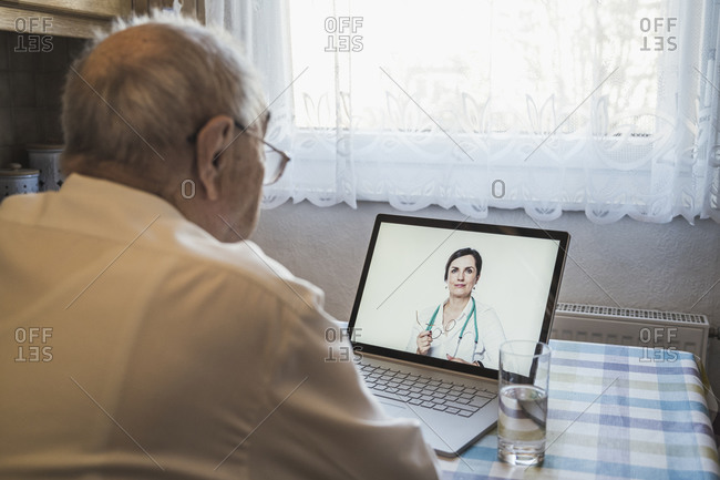 Senior man taking advice from female doctor through video call on laptop at home