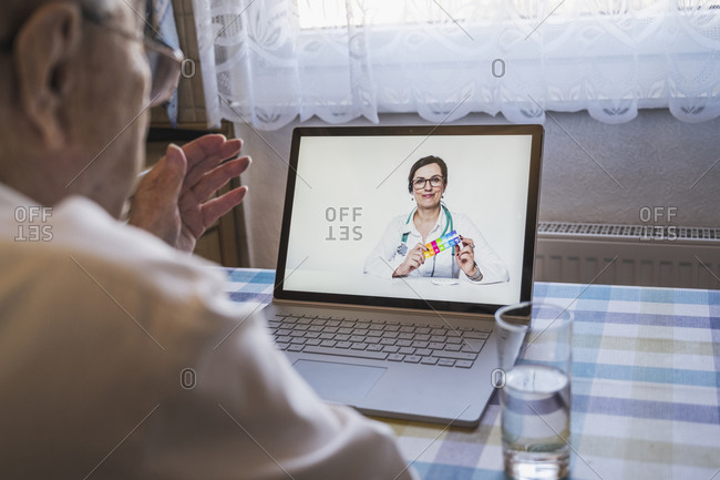Female general practitioner giving advice to senior man during video call at home