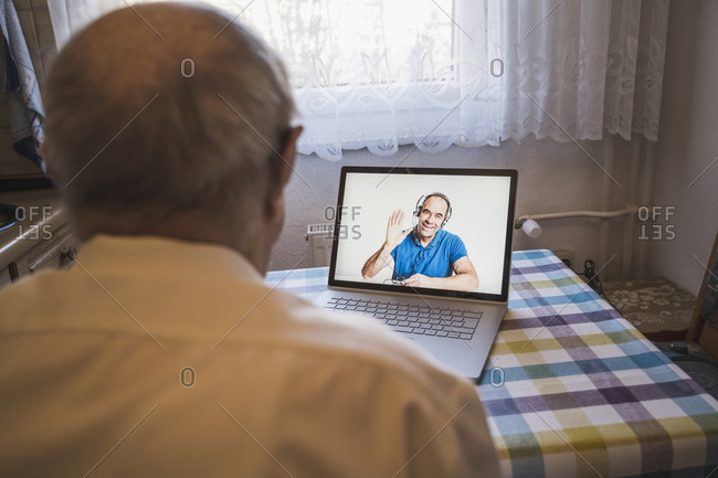 Mature man greeting senior man on video call through laptop at home