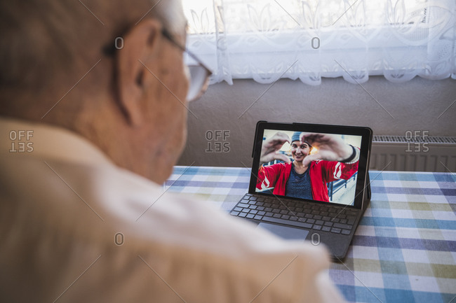Grandfather talking with granddaughter on video call through laptop at home