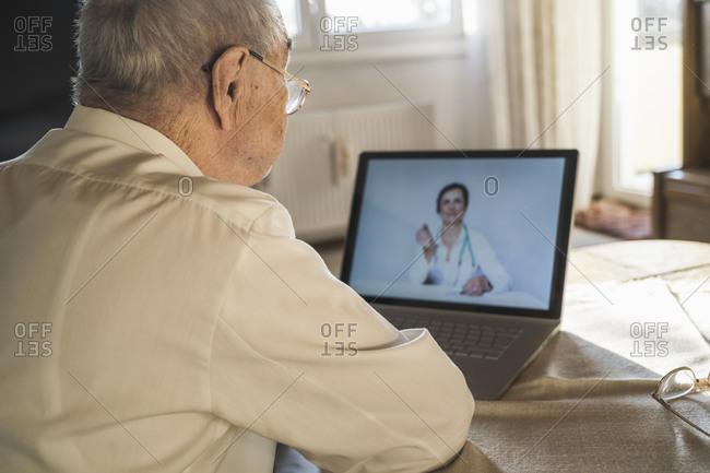 Senior man taking advice from female doctor on video through laptop in living room