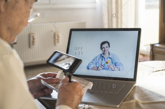 Senior man reading through magnifying glass while female doctor consulting on video call