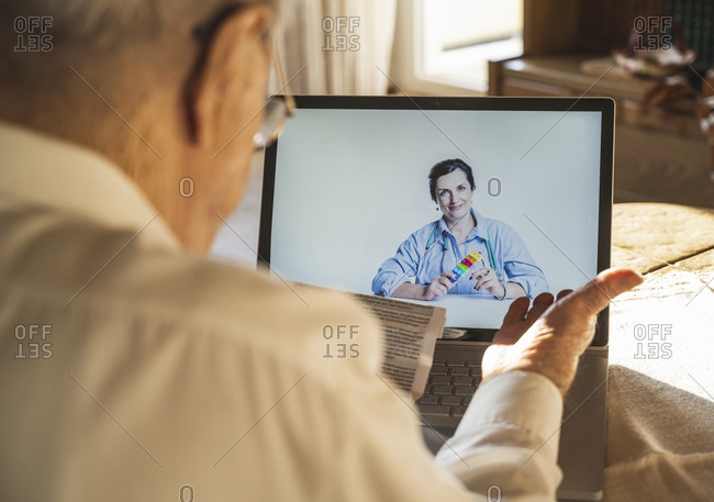 Male patient reading while female doctor consulting through video call on laptop at home
