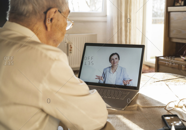 Female doctor giving advice to senior male patient during video call at home