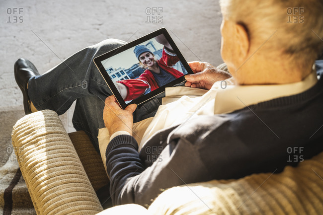 Grandfather talking with granddaughter on video call through digital tablet at home