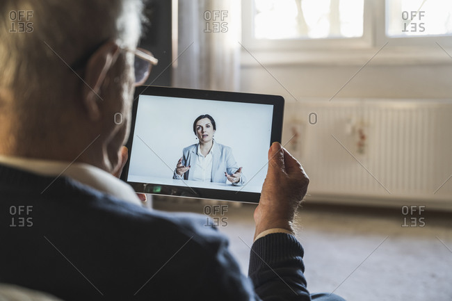 Female doctor consulting male patient on video call through digital tablet at home