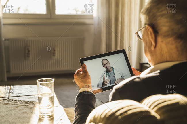 Male doctor consulting senior man on video call through digital tablet in living room