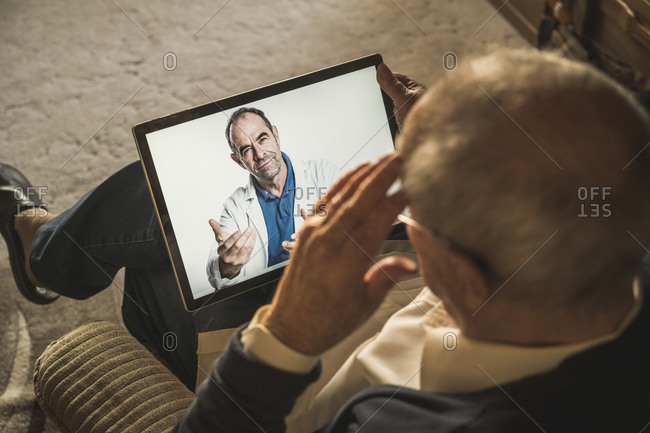 Elderly man talking with male doctor on video call at home