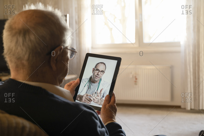 General practitioner consulting senior man online through digital tablet in living room