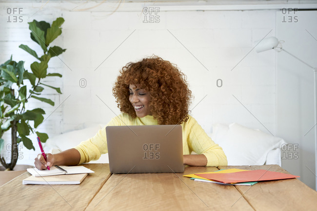 Happy businesswoman with laptop writing in notepad while working from home