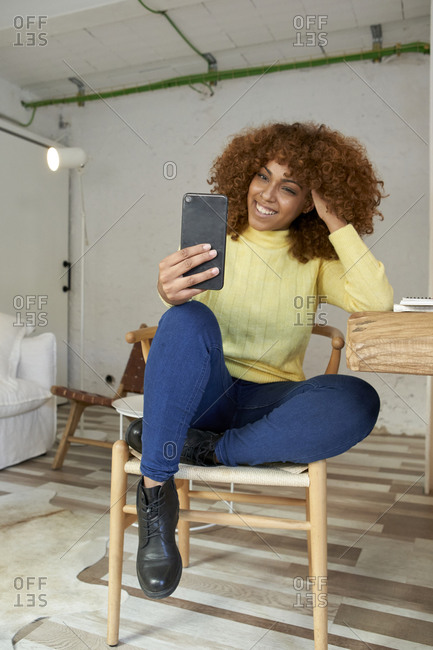 Businesswoman doing video call through mobile phone at home