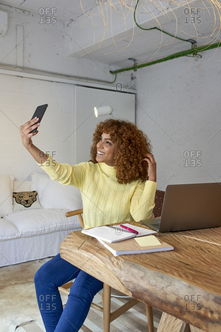 Smiling businesswoman with hand in hair taking selfie at home