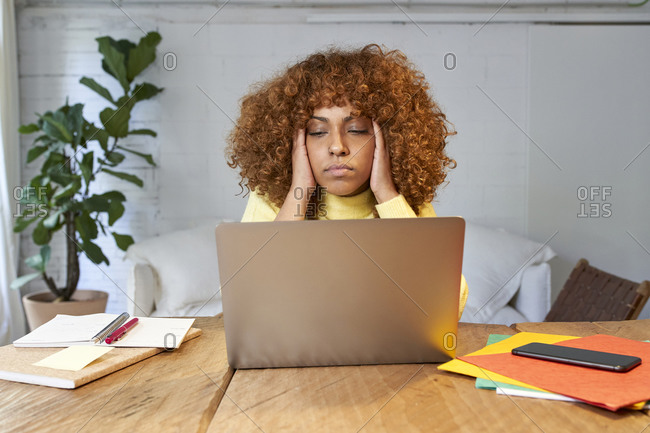 Exhausted businesswoman with headache working on laptop at home