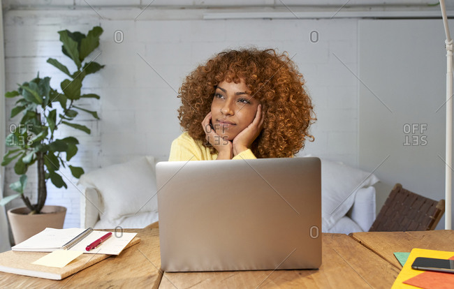 Young businesswoman day dreaming while working from home