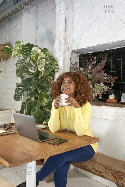 Smiling businesswoman day dreaming while holding coffee cup in cafe