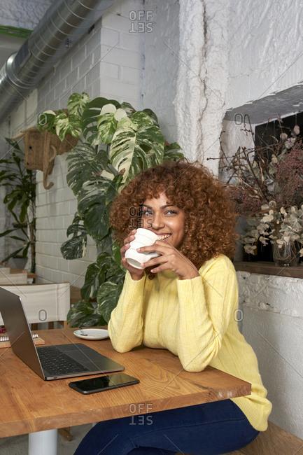 Happy female entrepreneur having coffee while looking away in coffee shop