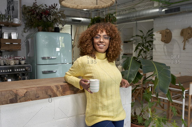 Smiling woman holding coffee cup while leaning on counter at cafe