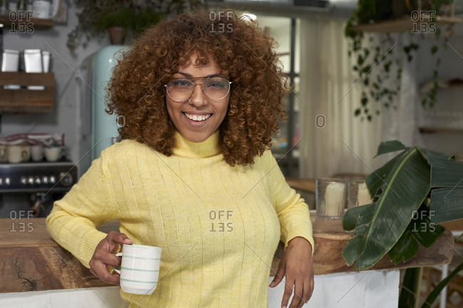 Smiling woman with coffee cup leaning on counter at cafe