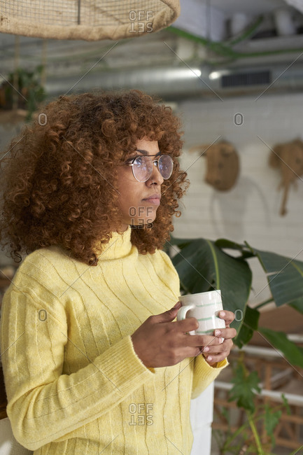 Thoughtful woman with coffee cup in cafe