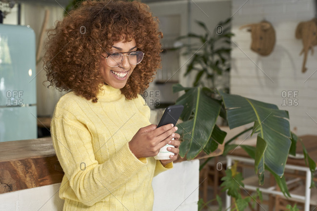 Smiling woman with coffee cup using smart phone at cafe