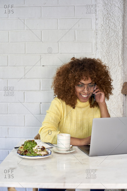 Smiling freelance worker with food and drink talking on phone call in cafe