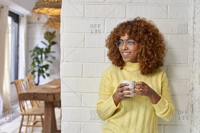Woman looking away while having coffee against brick wall in cafe