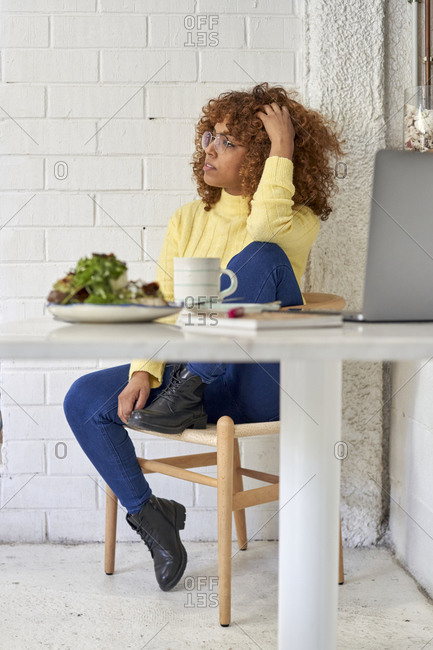 Female entrepreneur with hand in hair looking away while sitting in cafe