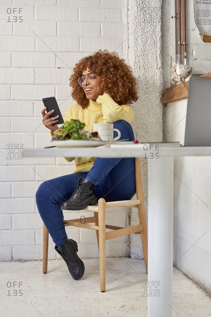 Happy businesswoman using smart phone while sitting on chair in cafe