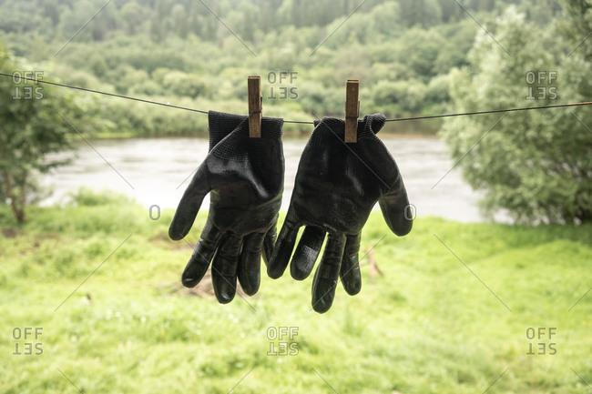 Two black gardening gloves hanging on clothesline