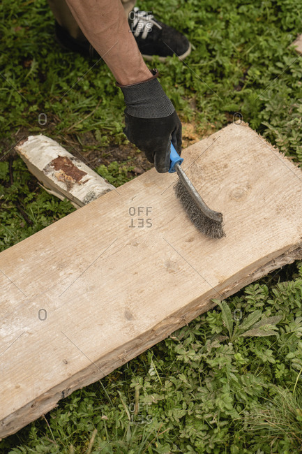 Hands of man brushing plank with wire brush