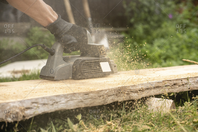 Hands of man sawing plank with circular saw