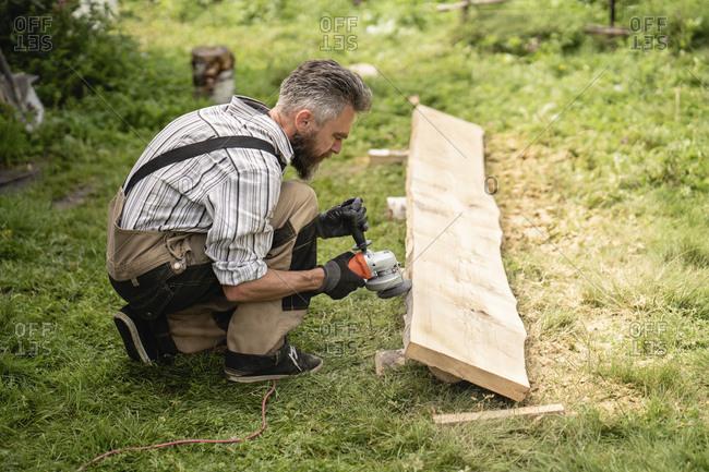 Carpenter grinding plank with hand grinder
