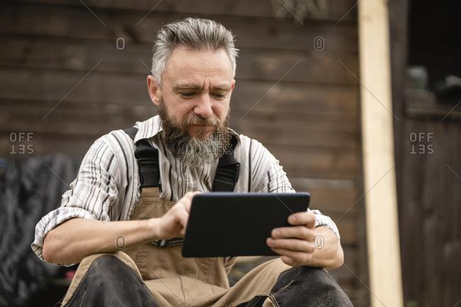 Portrait of carpenter using digital tablet during break