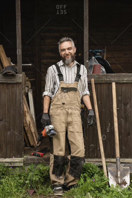 Portrait of bearded carpenter standing outdoors with grinder in hand