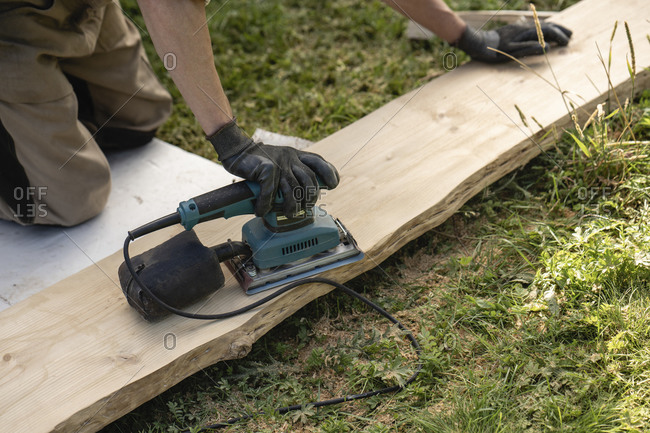 Hands of man grinding plank with hand grinder