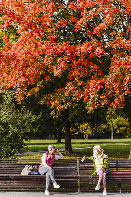 Mature female friends sitting on park bench while social distancing during COVID-19