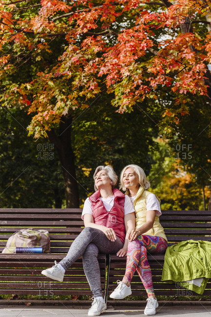 Female friends in sports clothing with eyes closed at autumn park on sunny day