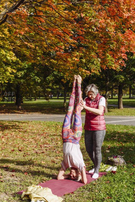 Mature woman helping female friend doing headstand in autumn park