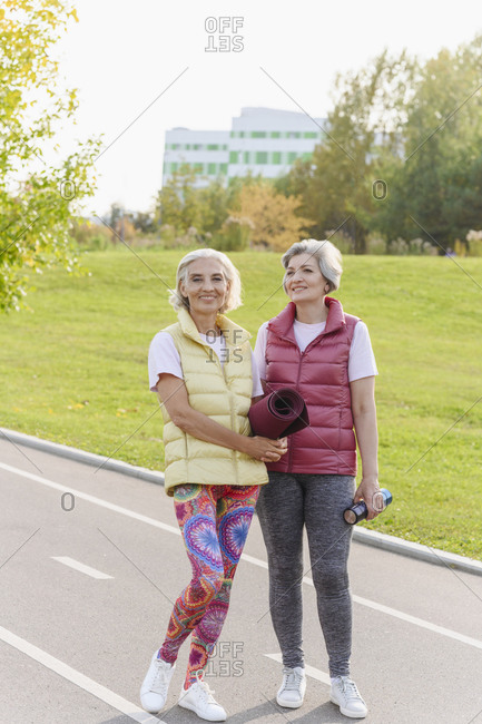 Smiling female friends in sports clothing at public park on sunny day