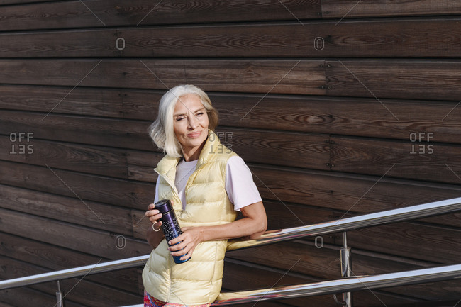 Smiling mature woman holding water bottle while leaning on railing against wood wall