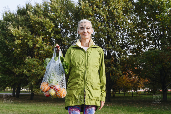 Mature woman holding mesh bag filled with fruits and vegetables at public park