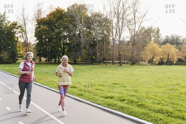 Smiling female friends jogging in public park on sunny day